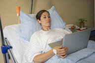 Female patient using laptop, resting and recovering in hospital room - FSIF03435