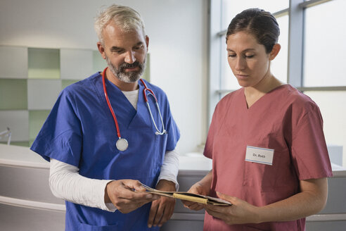 Doctors reviewing medical record in hospital - FSIF03438