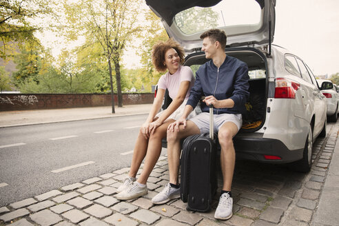 Young couple with suitcase sitting in car hatchback - FSIF03450