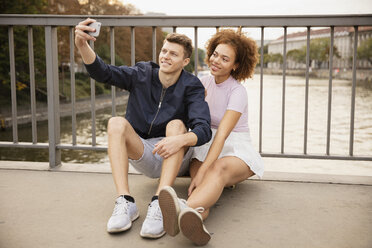 Young couple taking selfie with camera phone on urban bridge - FSIF03468