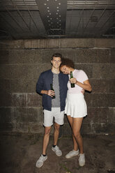 Portrait young couple drinking beer in basement - FSIF03474