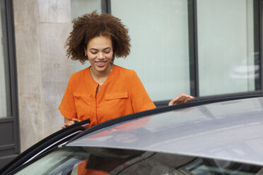 Young woman getting in car - FSIF03477