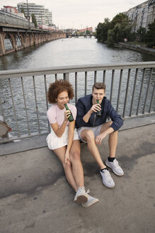 Young couple drinking beer on urban bridge over river - FSIF03483