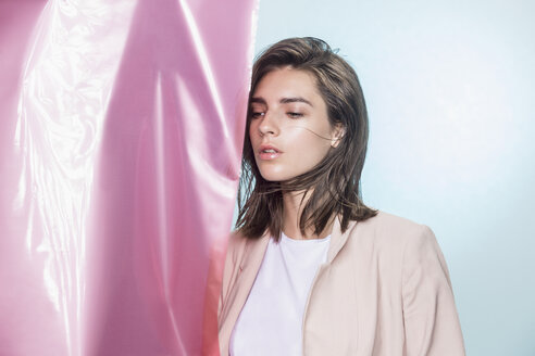 Portrait of a female fashion model posing with pink fabric and looking away - FSIF03522
