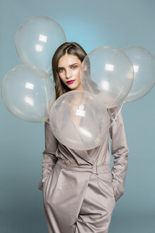 Portrait of female fashion model standing with balloons against blue background - FSIF03525