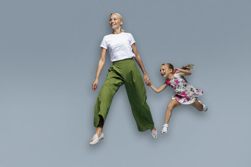 Mother and daughter running on blue background - FSIF03537