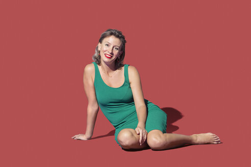 Portrait confident woman sitting on red background - FSIF03546