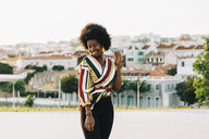 Smiling young woman standing on sunny street, Belem, Lisbon, Portugal - FSIF03627