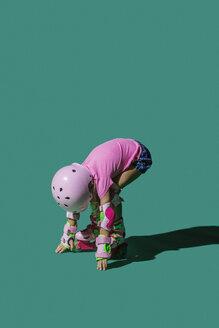 Girl roller skating against green background - FSIF03633