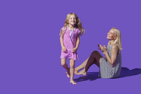 Portrait playful mother and daughter in striped dresses against purple background - FSIF03639