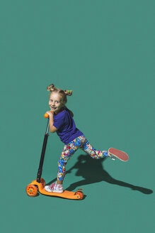 Playful girl riding scoter on green background - FSIF03645