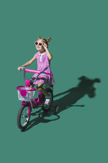Girl in sunglasses bike riding against green background - FSIF03657