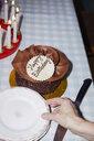 Woman reaching for plate next to chocolate birthday cake - FSIF03669