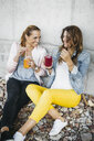 Two female friends drinking smoothies outdoors having fun - HMEF00164