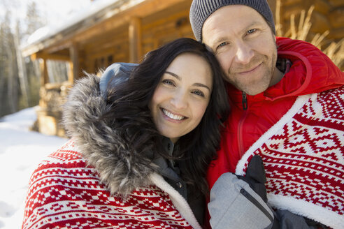 Portrait of romantic couple wrapped in blanket outdoors - HEROF00637