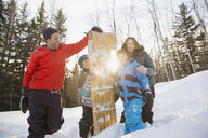 Portrait of smiling family and toboggan outdoors - HEROF00646