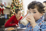 Portrait of boy drinking milk during Christmas - HEROF00649
