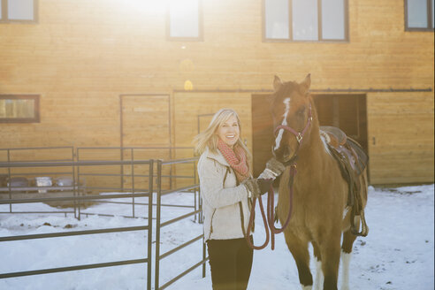 Portrait of smiling woman standing with horse in snow - HEROF00703