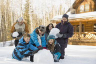Multi-generation family making snowman together - HEROF00820