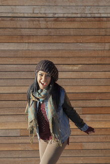 Playful woman standing against wood paneling outdoors - HEROF00823