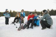 Multi-generation family taking a break from snowshoeing - HEROF00880