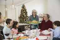 Grandmother serving turkey to family at Christmas dinner - HEROF00895