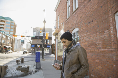 Man text messaging on city street - HEROF00943