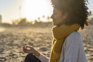Woman sitting on the beach at sunset, meditating - AFVF02115