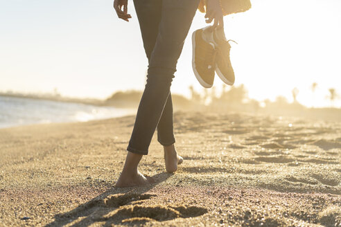 Barefoot woman on the beach, carrying her shoes - AFVF02118