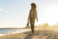 Barefoot woman on the beach, carrying her shoes - AFVF02121