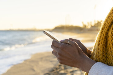 Woman with yellow scarf, using smartphone on the beach - AFVF02130