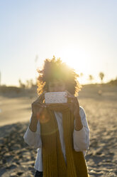 Woman with yellow scarf, using smartphone on the beach - AFVF02133