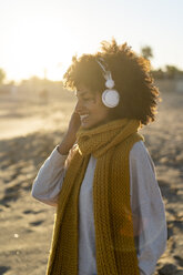 Woman with yellow scarf, listening music on the beach - AFVF02136