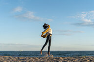 Woman jumping on the beach, wearing headphones, listening music - AFVF02142