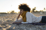 Woman lying in the sand, relaxing on the  beach, reading a book - AFVF02151