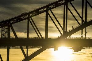 Australia, Sydney, Tourists climbing Sydney harbour bridge at sunset - RUNF00430