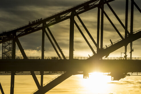 Australia, Sydney, Tourists climbing Sydney harbour bridge at sunset - RUNF00430