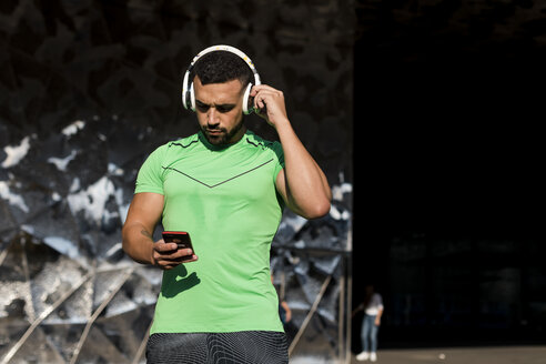 Sportive man during workout, using smartphone and headphones - MAUF01963