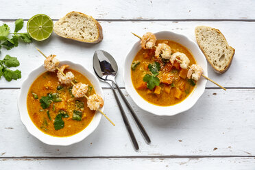 Two bowls of sweet potato soup with  shrimps, coconut flakes and fresh coriander - SARF04022