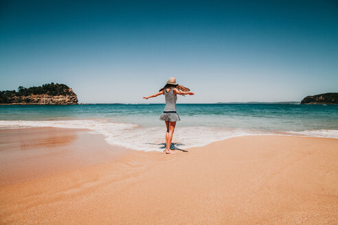 A woman standing at the beach under blue skies - INGF10396