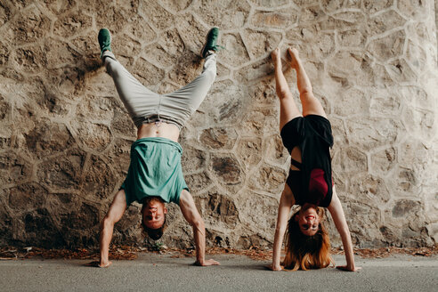 Two people doing handstands against a brick wall - INGF10444