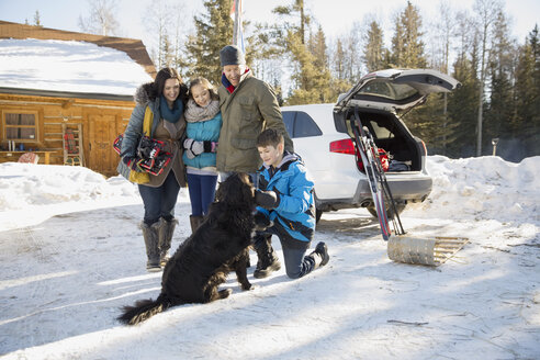 Family gathered outside log cabin in winter - HEROF01017