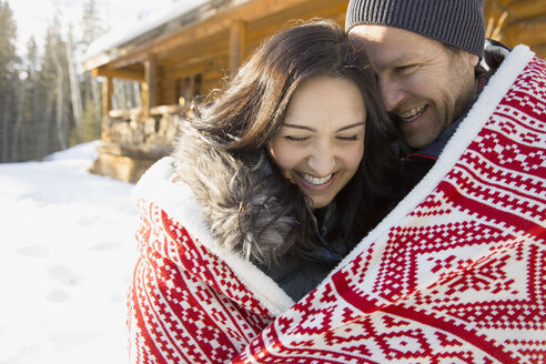 Couple wrapped in blanket outdoors during winter - HEROF01047