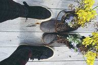 A person standing in front of old boots filled with flowers - INGF10626