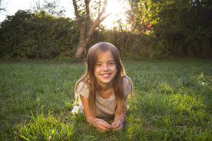 Portrait of smiling little girl lying on a meadow at evening twilight - LVF07610