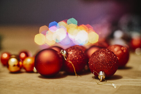 Red Christmas baubles on wooden floor, close-up - BZF00470