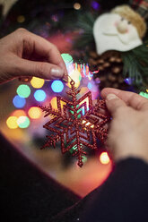 Woman's hand holding Christmas ornament, close-up - BZF00473