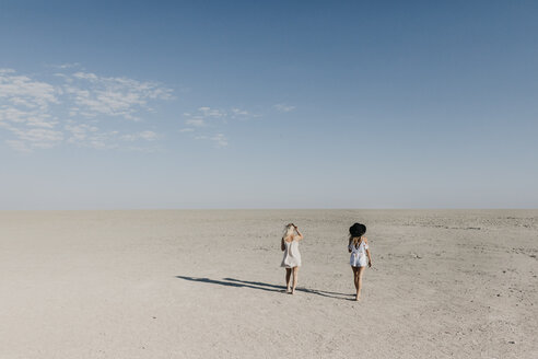 Two young women walking in the desert - LHPF00209