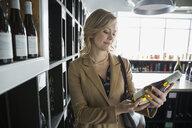Woman reading label on bottle in wine store - HEROF01277