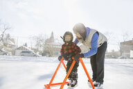 Son using assistant rack on ice hockey rink - HEROF01280